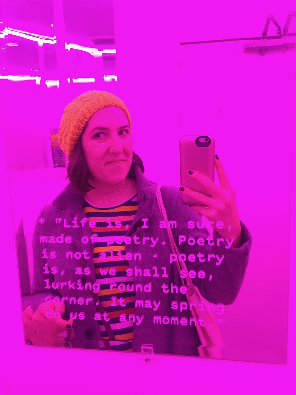 Women taking a photo in a mirror in a pink neon bathroom with quotes by Jorge Louis Borges on the mirrors