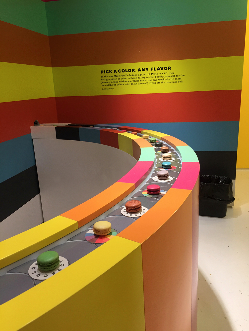 Rainbow macaroon conveyor belt installation at the Color Factory in New York City, New York