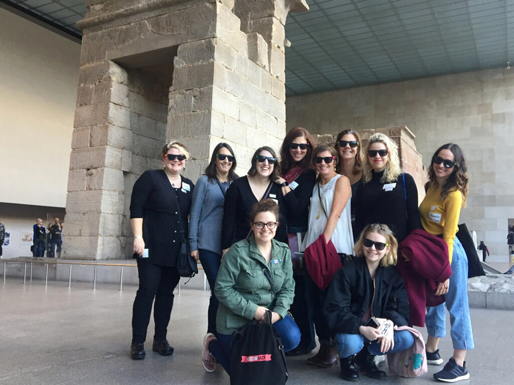 Group of people on a Museum Hack tour in front of an Egyptian tomb at the Metropolitan Museum of Art in New York City
