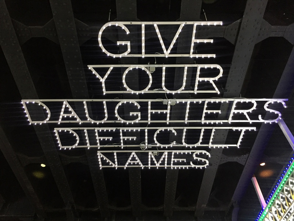"""Installation made from lights that says """"Give your daughters difficult names"""" outside the Whitney Museum of American Art in New York City"""