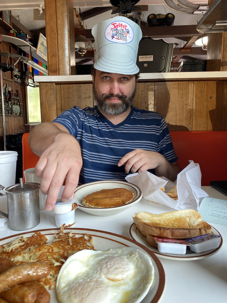 Man wearing paper hat with eggs, hash browns and pancakes at Fritz's Railroad Restaurant in Kansas City, Kansas