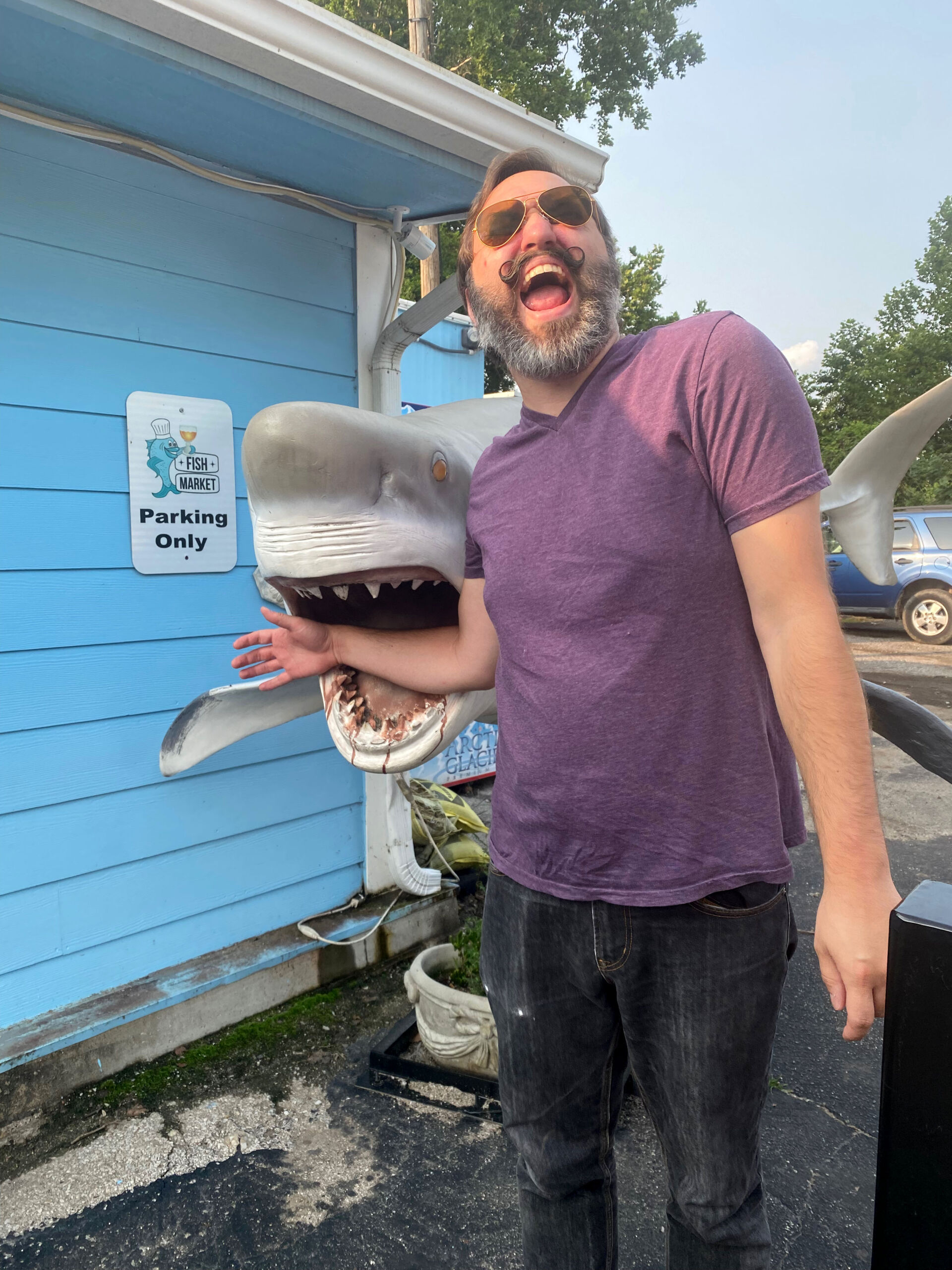 Man with mustache pretending to be bitten by shark statue at The Fish Market in Liberty, Missouri